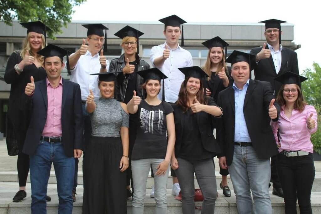 Auf dem Bild: Die Absolventen des Social Media Manager IHK Dortmund Vollzeitkurs tragen ihre Doktorh¸te und halten den ausgestreckten Daumen in die Kamera