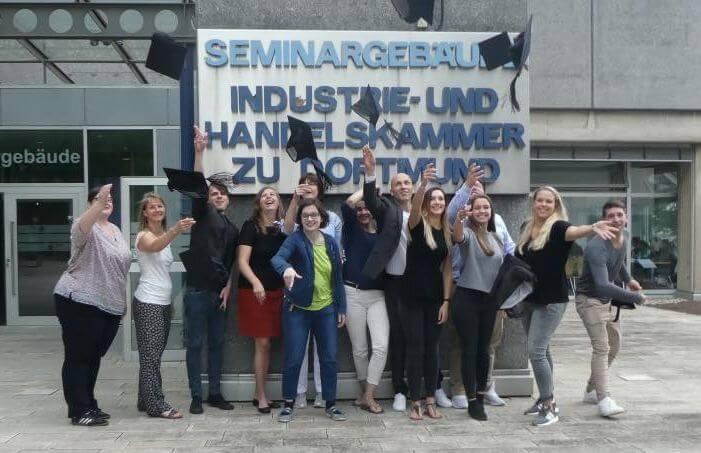 Das Bild zeigt die Teilnehmer im Social Media Manager IHK Dortmund Teilzeitkurs, wie sie ihre Doktorhüte in die Luft werfen