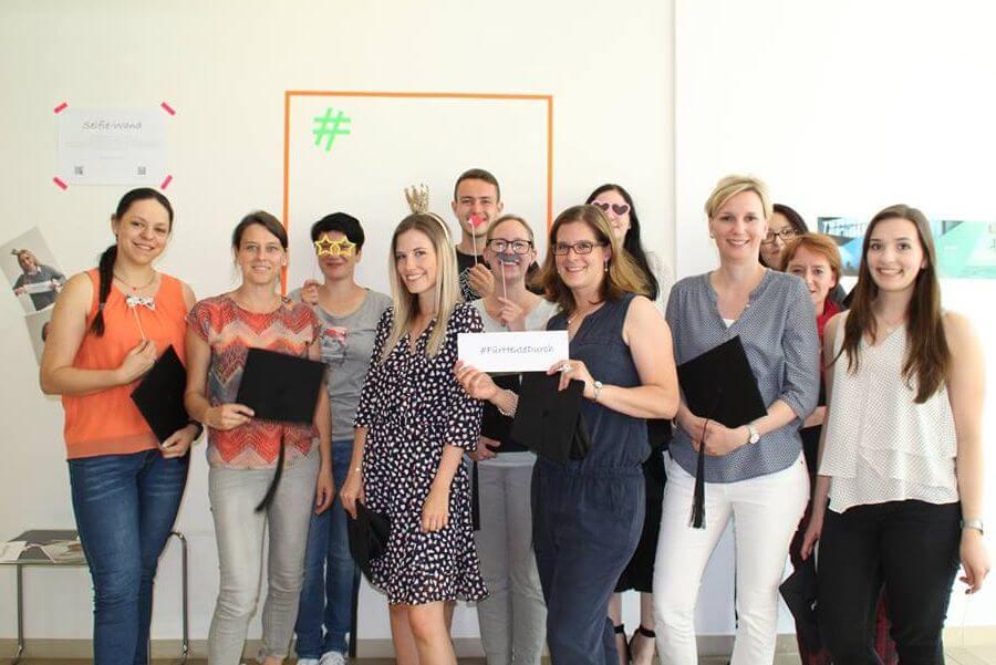 Auf dem Bild sind die 12 Absolventen im Social Media Manager IHK Mittleres Ruhrgebiet Onlinekurs zu sehen. Sie lächeln in die Kamera.