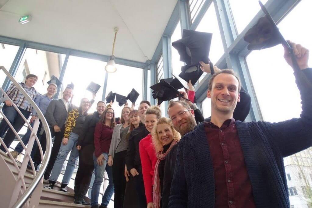 Auf dem Foto: Die Absolventen im Social Media Manager IHK Mittleres Ruhrgebiet Onlinekurs stehen auf der Treppe der IHK und heben ihre Doktorhüte in die Höhe