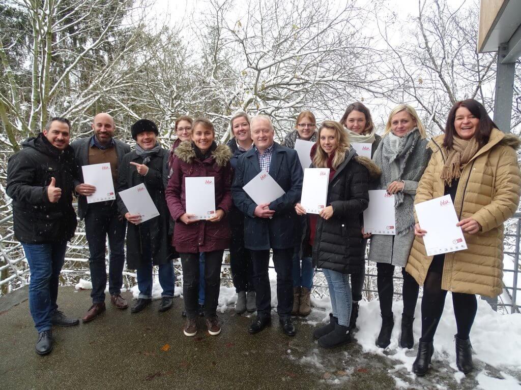 Das Bild zeigt die 12 Social Media Manager IHK Siegen Onlinekurs, wie sie ihre Zertifikate in die Kamera halten.