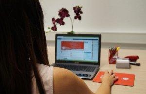 Eine junge Frau bei der Internetrecherche zu einem Unternehmen. Sie soll das Unternehmen Dank Social Recruiting finden und sich bewerben.