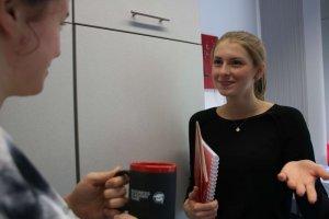 Ein guter Team Zusammenhalt ist ein Faktor für die Mitarbeitermotivation. Das Bild zeigt zwei Kolleginnen im Gespräch.