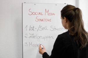 Braucht meine Branche Social Media Marketing? Vor diesem Hintergrund zeigt das Bild eine Frau, die an einem Whiteboard steht und Stichpunkte für eine Marketingstrategie notiert.