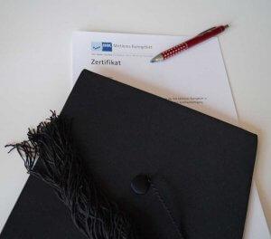 Das Bild zeigt einen Doktorhut und ein Zertifikat. All dies winkt, wenn man die betriebliche Weiterbildung durchlaufen hat
